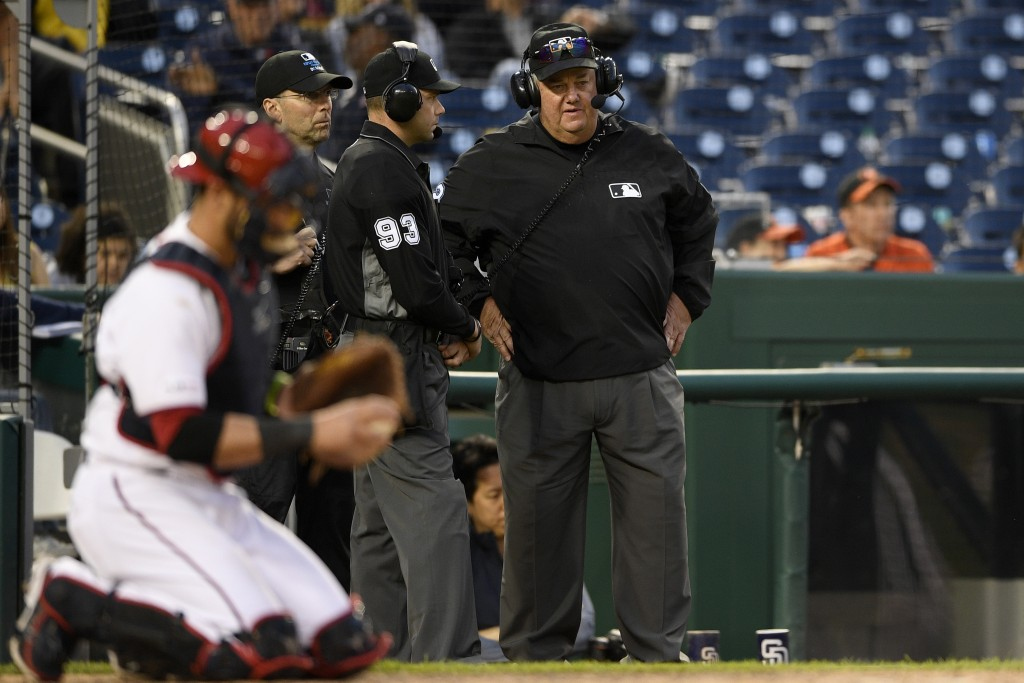 Umpire Joe West, right, and home plate umpire Will Little (93) wear headphones during a review of a play during the 10th inning of a baseball game bet...