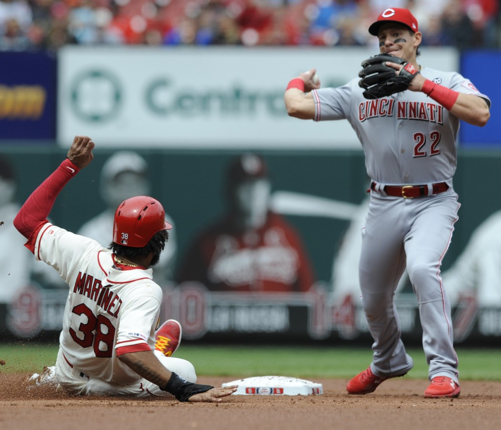Cincinnati Reds' Derek Dietrich (22) forces out St. Louis Cardinals' Jose Martinez (38) and completes a double play by getting Yadier Molina at first ...