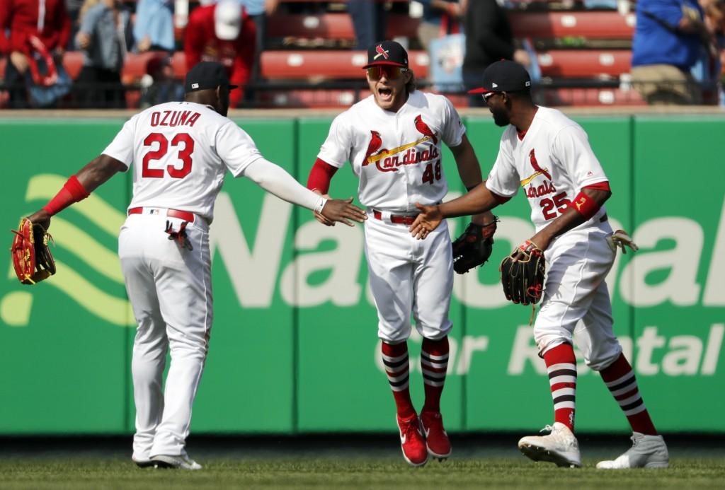 St. Louis Cardinals' Marcell Ozuna (23), Harrison Bader (48) and Dexter Fowler (25) celebrate following a victory over the Cincinnati Reds in a baseba...