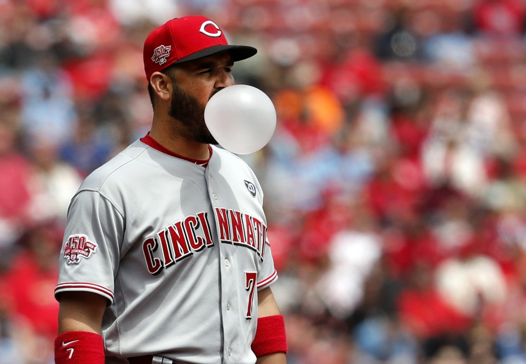Cincinnati Reds third baseman Eugenio Suarez blows a bubble between pitches during the second inning of a baseball game against the St. Louis Cardinal...