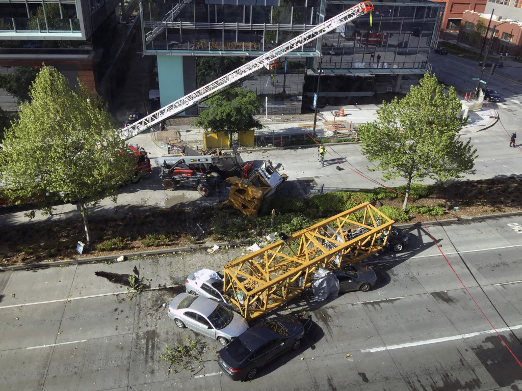 Fire and police crew members work to clear the scene where a construction crane fell from a building on Google's new Seattle campus crashing down onto...