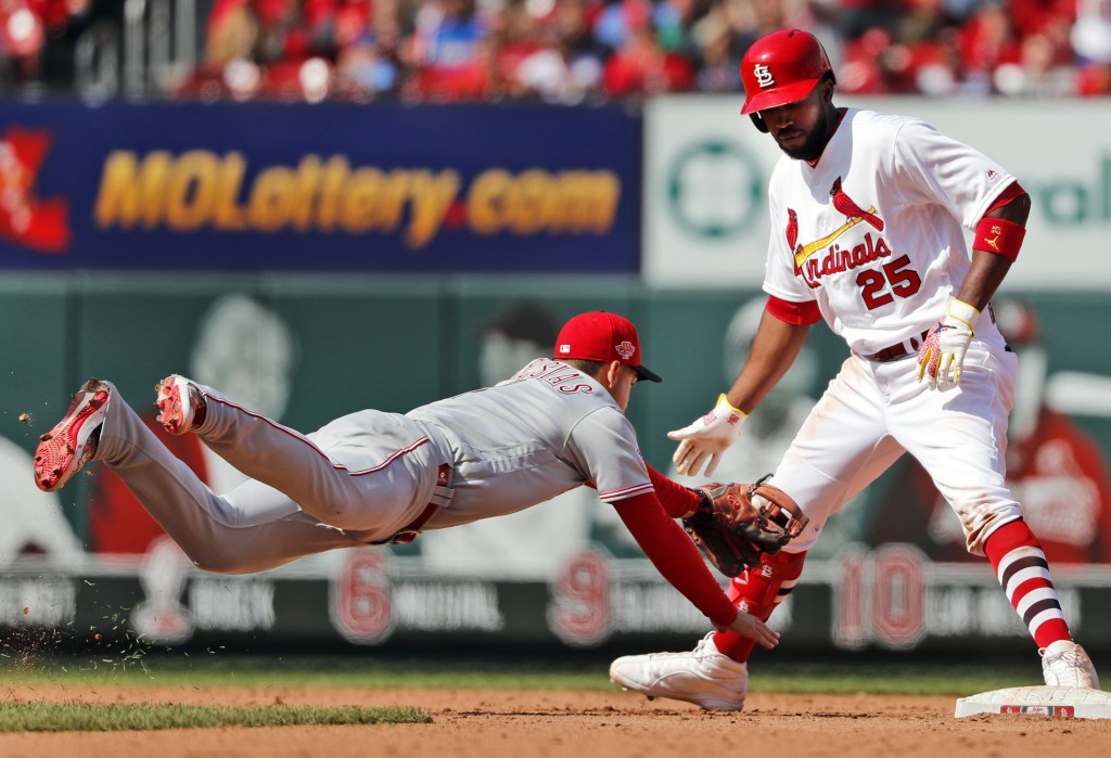Cincinnati Reds shortstop Jose Iglesias, left, dives to tag out St. Louis Cardinals' Dexter Fowler (25) when Fowler's foot came off the bag after hitt...