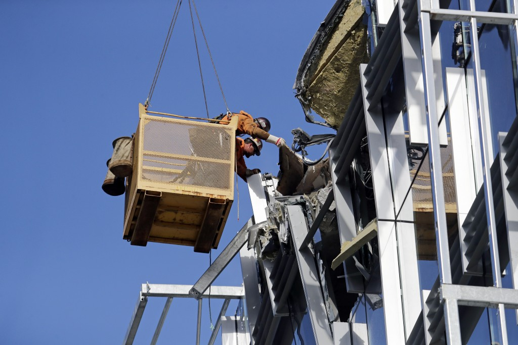 Workers suspended in a basket reach out toward debris from a building damaged when the crane atop it collapsed a day earlier, Sunday, April 28, 2019, ...