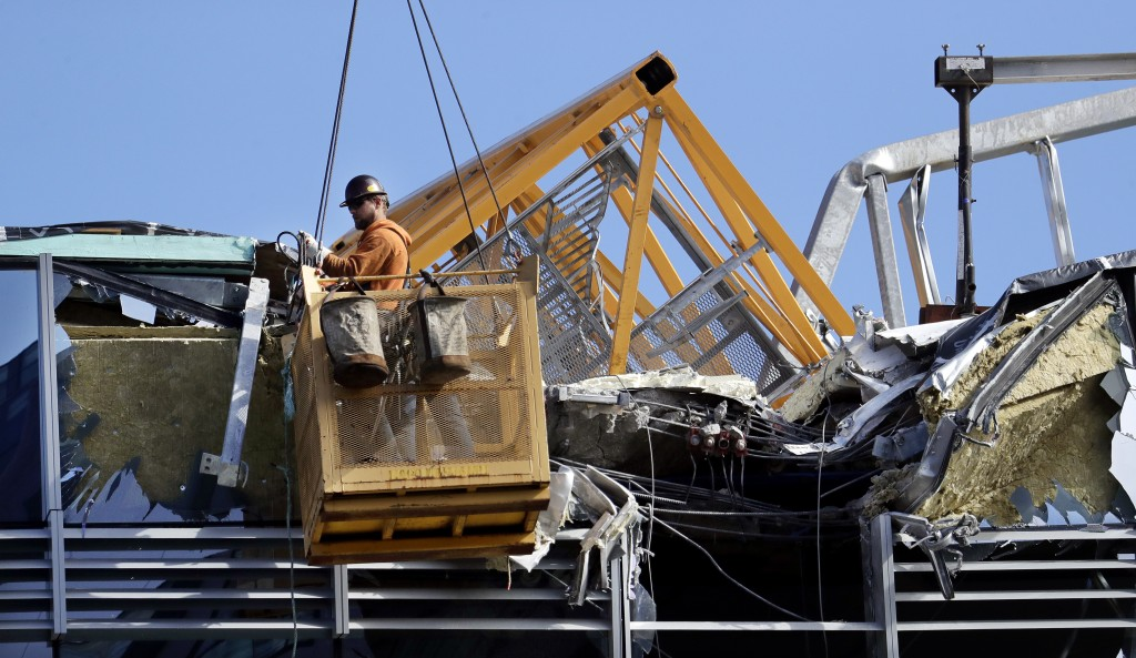 With a portion of the broken crane on the roof behind, a worker suspended in a basket clears debris from a building damaged when the crane atop it col...