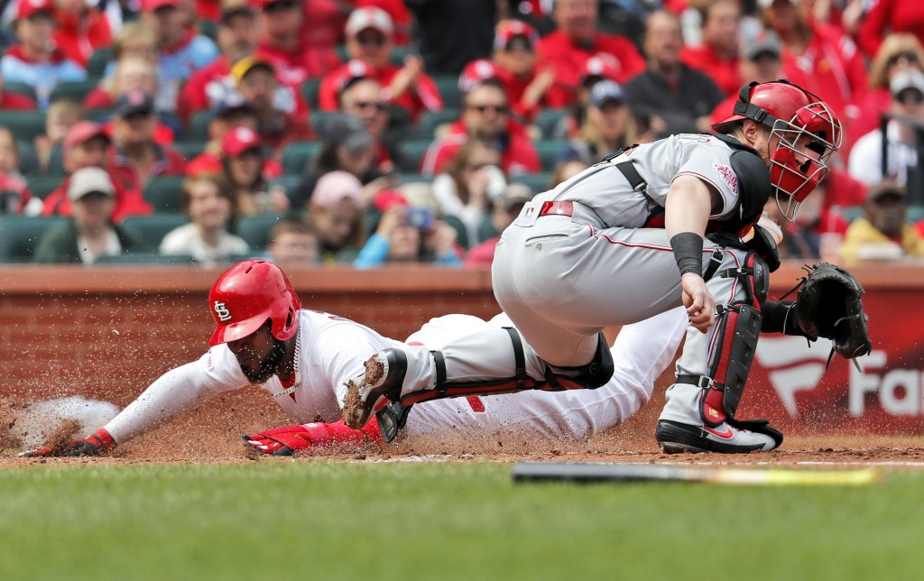 St. Louis Cardinals' Marcell Ozuna, left, scores past Cincinnati Reds catcher Tucker Barnhart during the fourth inning of a baseball game Sunday, Apri...