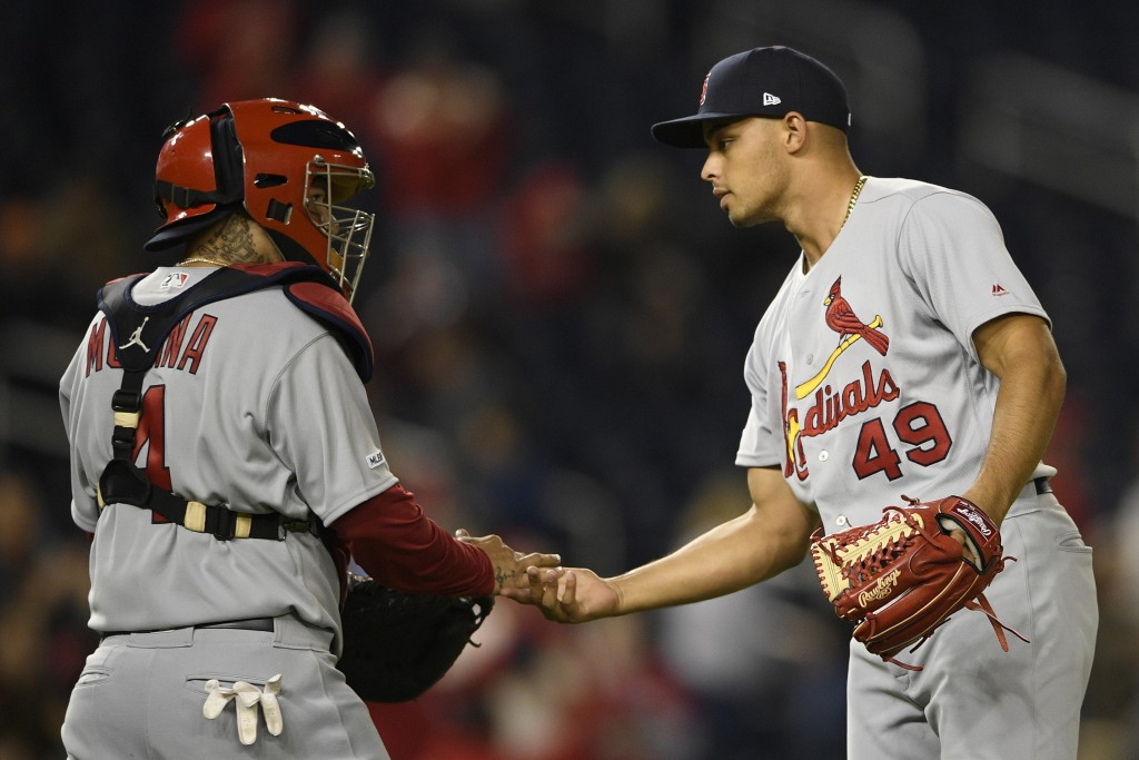 St. Louis Cardinals relief pitcher Jordan Hicks (49) celebrates with catcher Yadier Molina (4) after a baseball game against the Washington Nationals,...