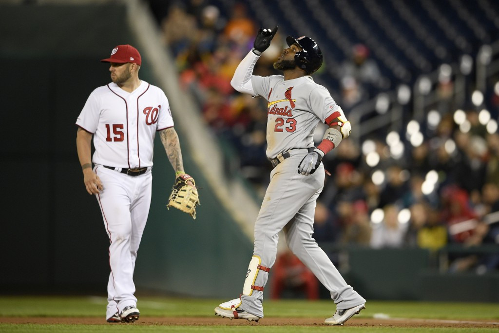 St. Louis Cardinals' Marcell Ozuna (23) reacts next to Washington Nationals first baseman Matt Adams (15) after hitting a single during the seventh in...