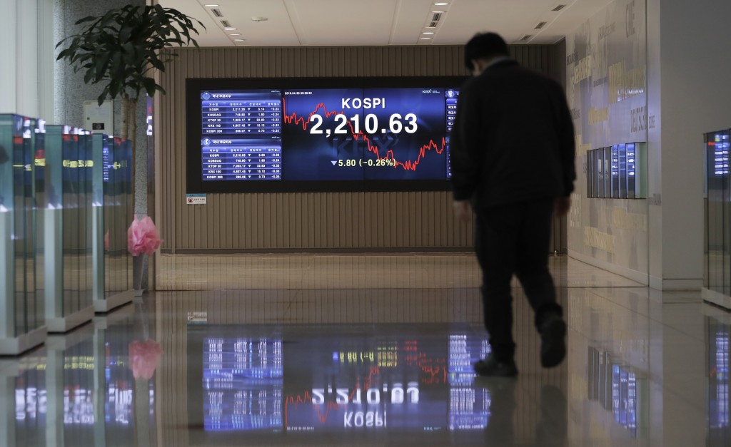 A man walks near a screen showing the Korea Composite Stock Price Index (KOSPI) at the Korea Exchange in Seoul, South Korea, Tuesday, April 30, 2019. ...