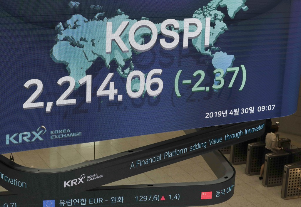 A woman walks near under a screen showing the Korea Composite Stock Price Index (KOSPI) at the Korea Exchange in Seoul, South Korea, Tuesday, April 30...