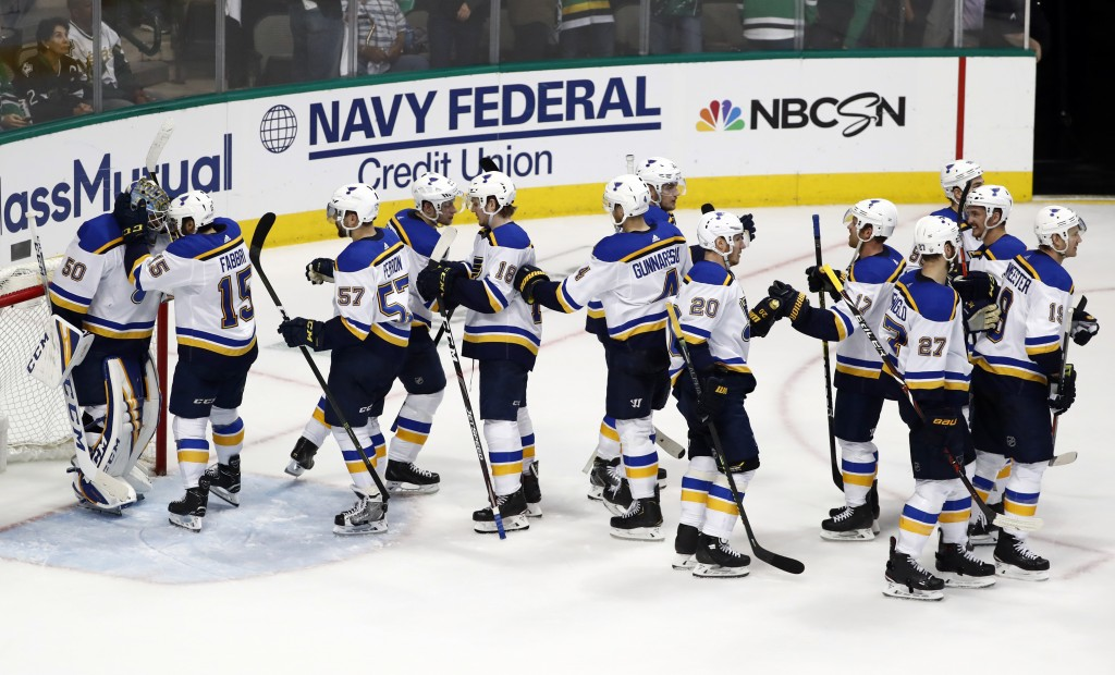 St. Louis Blues' Jordan Binnington (50) is congratulated by Robby Fabbri (15) and the rest of the team after their win against the Dallas Stars in Gam...