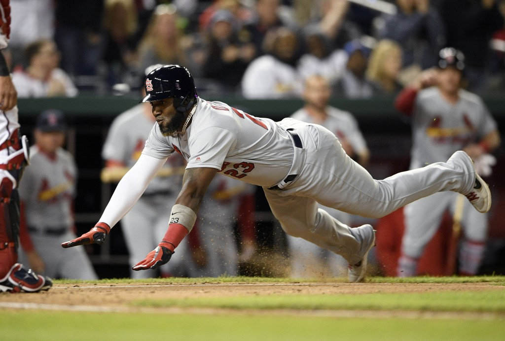 St. Louis Cardinals' Marcell Ozuna, right, starts his slide toward home to score on a double by Jose Martinez during the fifth inning of a baseball ga...