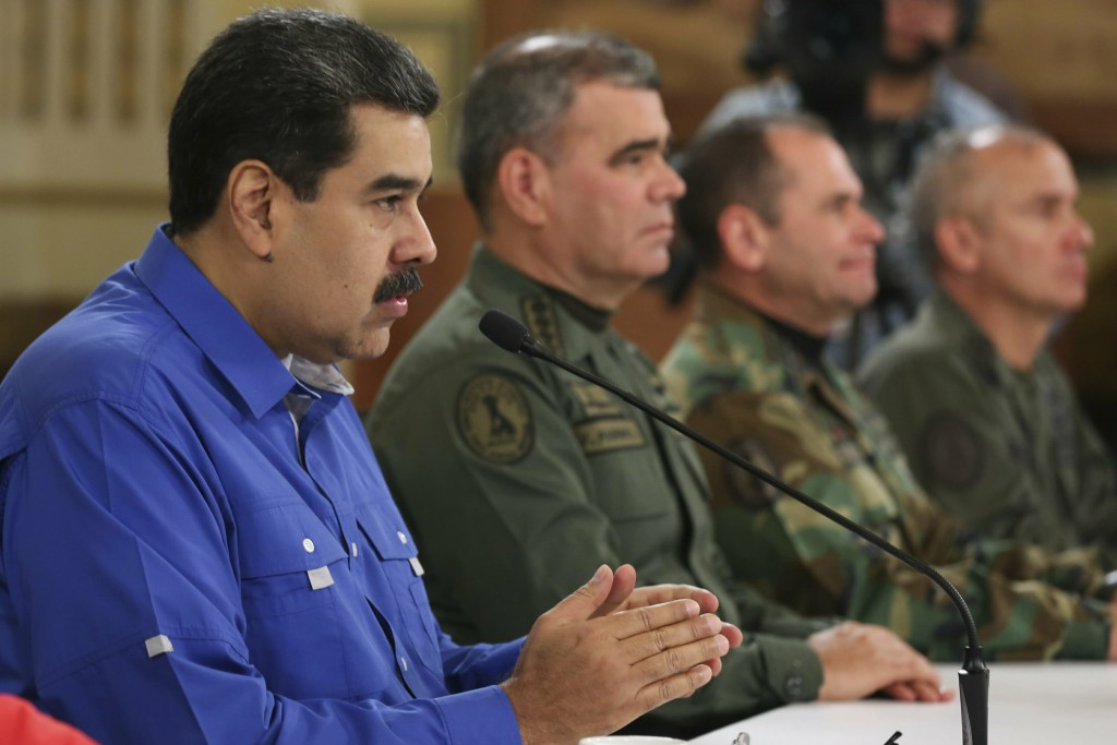 In this photo released by the Miraflores Press Office, Venezuela's President Nicolas Maduro, left, flanked by Venezuela's Defense Minister Gen. Vladim...