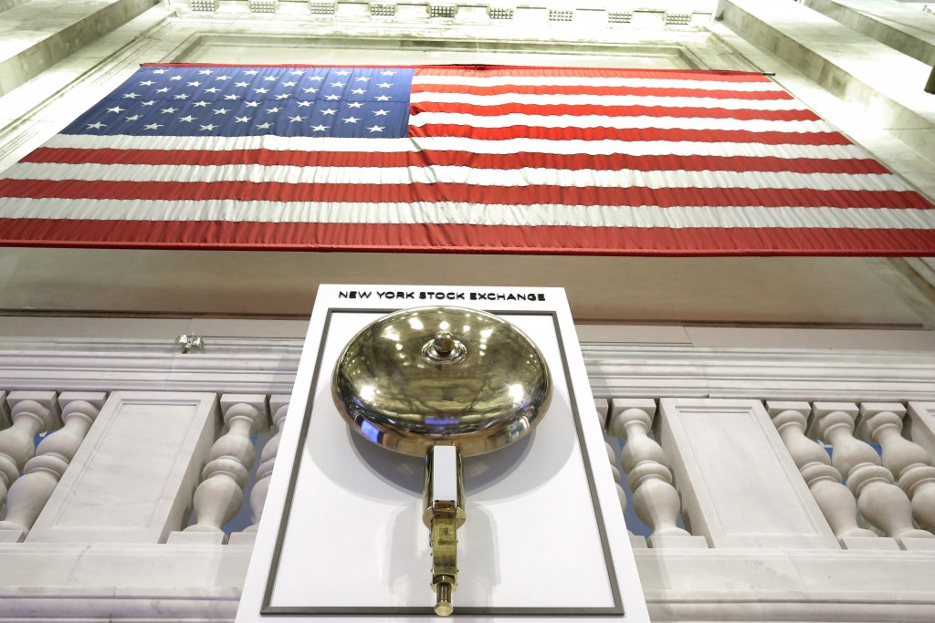 FILE- In this May 17, 2018, file photo an American flag hangs above the bell podium on the floor of the New York Stock Exchange. The U.S. stock market...