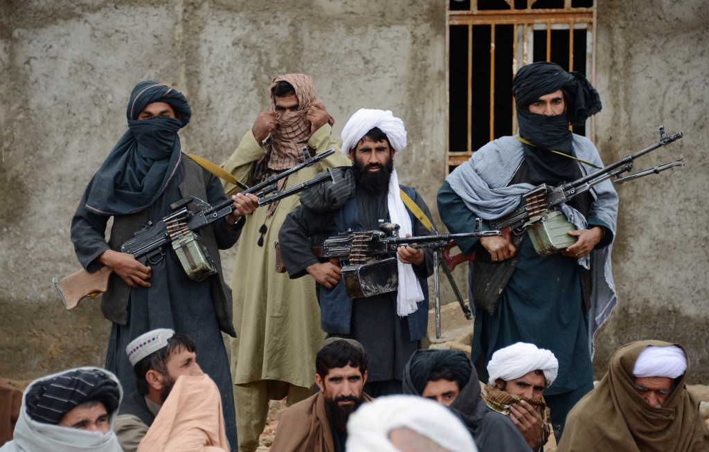 FILE - In this Nov. 3, 2015 file photo, Afghan Taliban fighters listen to Mullah Mohammed Rasool, the newly-elected leader of a breakaway faction of t