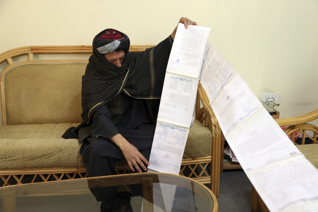 In this Sunday, April 28, 2019, photo, Aman, a former Taliban fighter from northern Kunduz province, shows letters he wrote seeking redress after he l