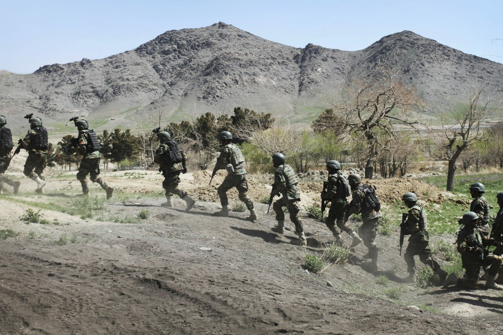 FILE - In this April 12, 2012, file, photo, Afghan special forces run after demonstrating a raid for rescuing a hostage at the commando training cente