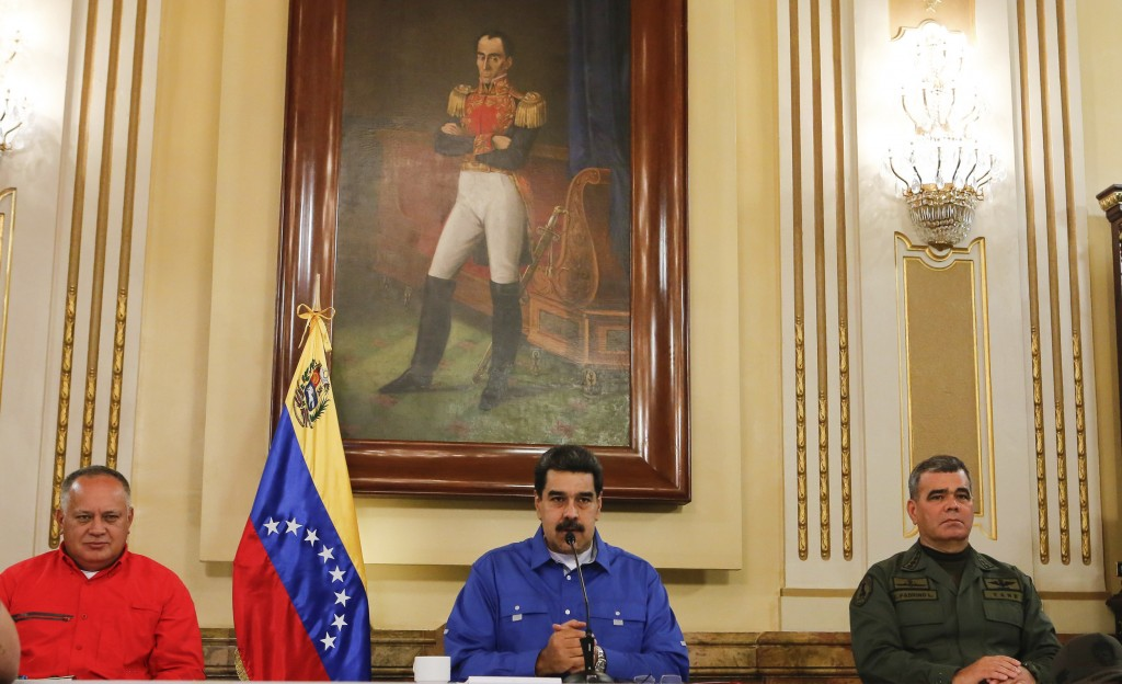 In this photo released by the Miraflores Press Office, Venezuela's President Nicolas Maduro, center, flanked by Venezuela's Defense Minister Gen. Vlad