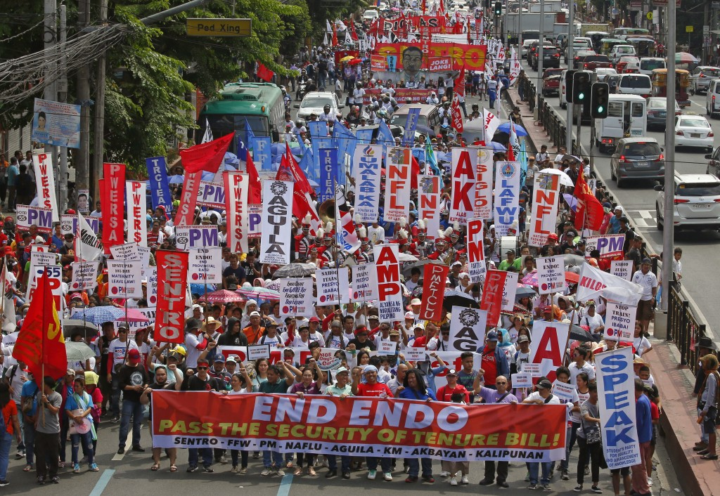 Thousands of workers march towards the Presidential Palace in Manila to pay tribute to workers in celebration of International Labor Day Wednesday, Ma...