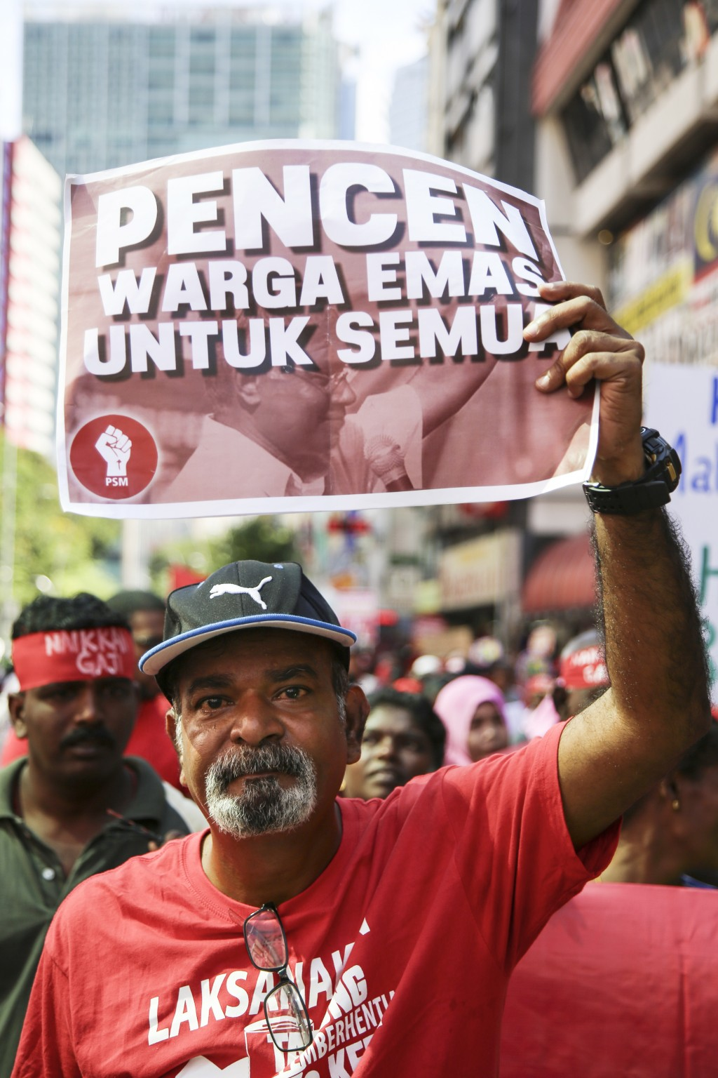 A man holds a sign during a May Day rally in Kuala Lumpur, Malaysia, Wednesday, May 1, 2019. Hundreds of workers demand raise of basic salary and endi