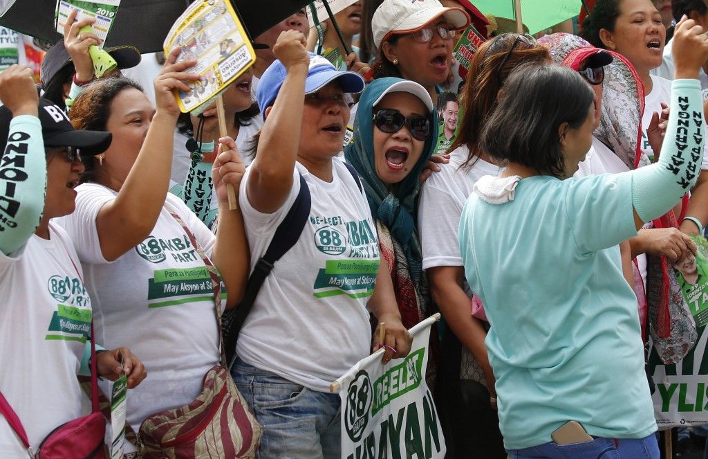 Protesters, mostly workers, shout slogans as they gather for a rally prior to marching towards the Presidential Palace in Manila to pay tribute to wor