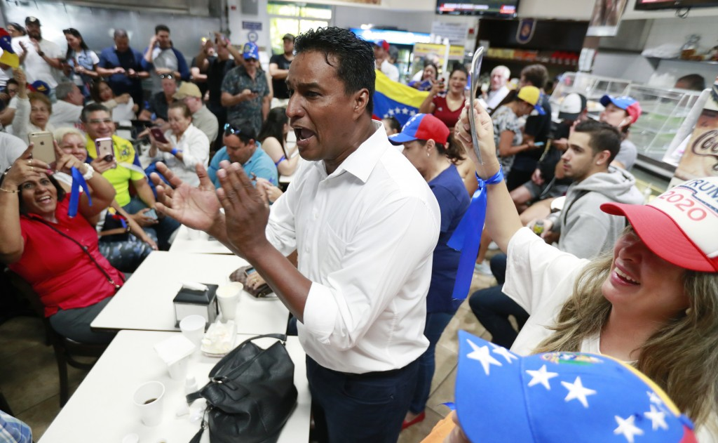 Venezuelan exile and former political prisoner Delson Guarte, the ex-mayor of Mario Briceño Iragorry Municipality, chants as he and others watch telev