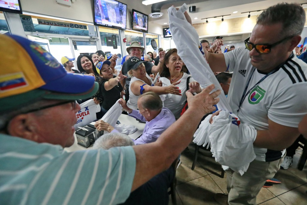 Venezuelans vie for T-shirts as they watch televised news from their country at the El Arepazo Doral Venezuelan restaurant, Tuesday, April 30, 2019, i