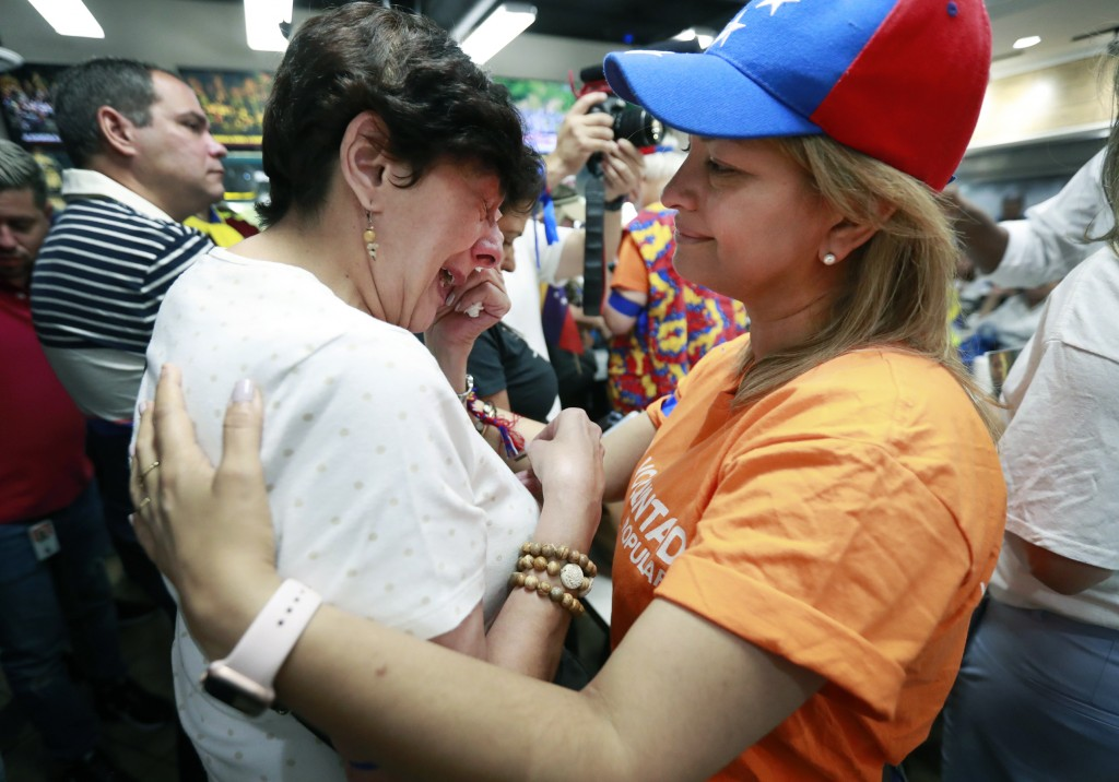 Rita Sanchez, right, comforts Miriam Abraham as they and other Venezuelans watch televised news from their country at the El Arepazo Doral Venezuelan
