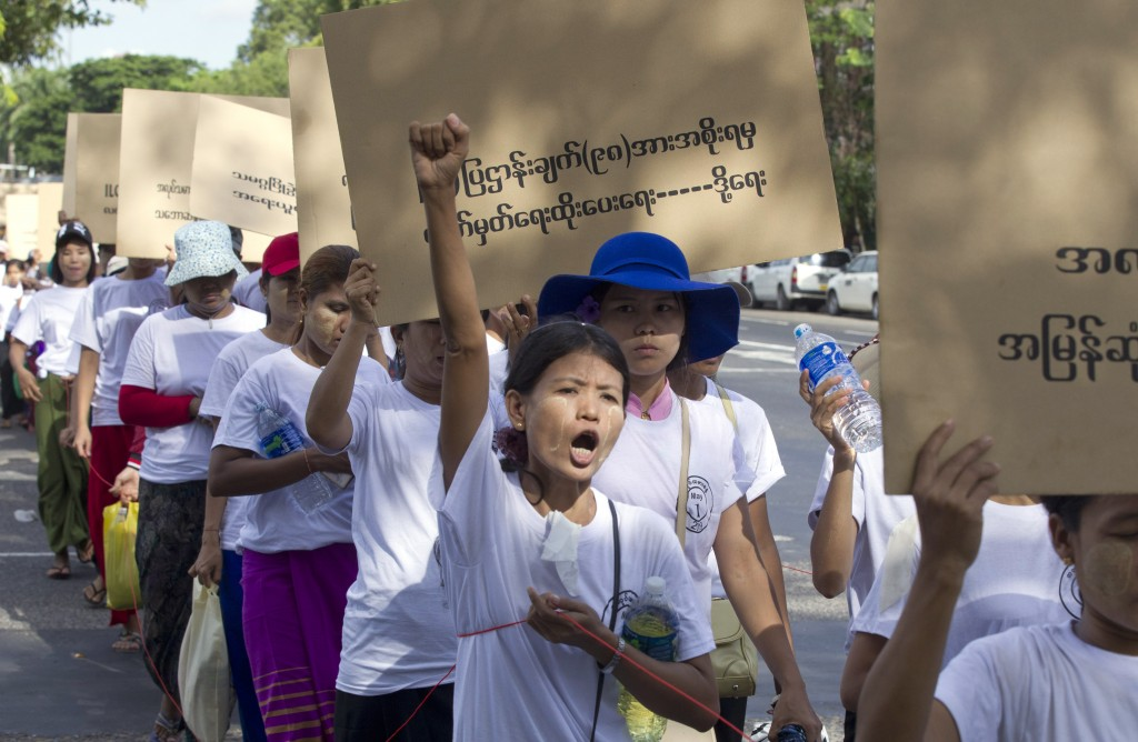 "Myanmar workers holding a placard read, ""Government to sign 98 facts of ILO law,"" shout slogans during a marching ceremony Wednesday, May 1, 2019, in"