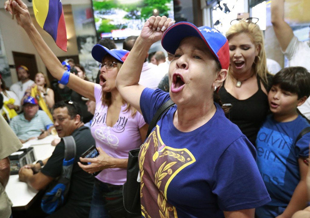 Arelys Lopez, foreground, leads a cheer as Venezuelans chant while watching televised news from their country at the El Arepazo Doral Venezuelan resta