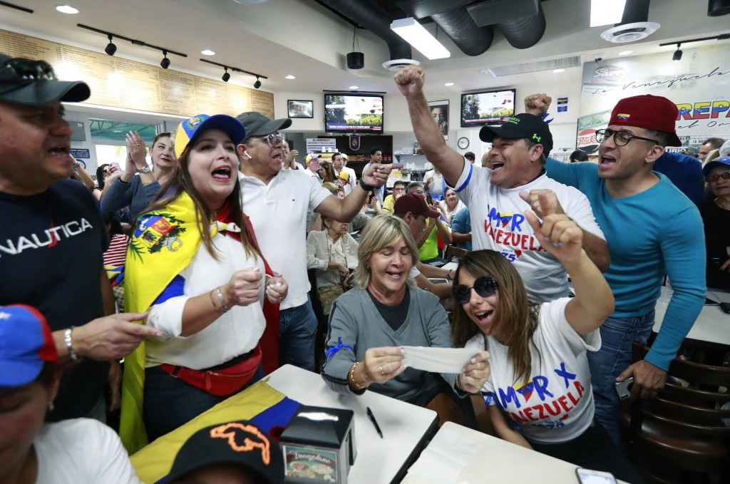 Venezuelans chant as they watch televised news from their country at the El Arepazo Doral Venezuelan restaurant, Tuesday, April 30, 2019, in Doral, Fl
