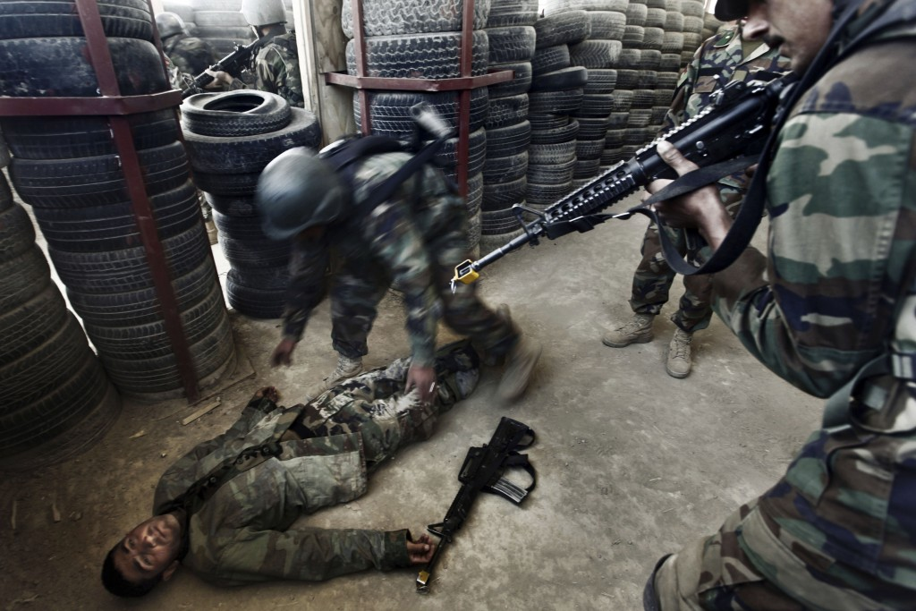 FILE - In this Tuesday, March 22, 2011 file photo, Afghan National Army commandos practice a house clearing during a training session at Camp Morehead...