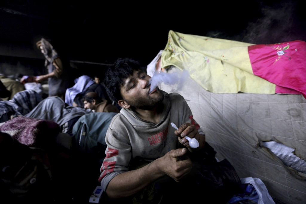 FILE - In this Wednesday, April 15, 2015, file, photo, an Afghan drug addict smokes heroin, in Kabul, Afghanistan. Afghanistan may not be ready for pe