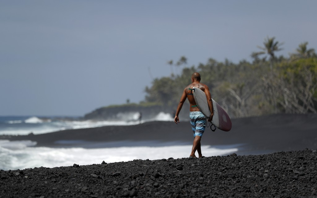 ADVANCE FOR RELEASE FRIDAY, MAY 3, 2019 AT 12:01 A.M. EDT AND THEREAFTER. In this Tuesday, April 23, 2019 photo, a surfer walks on a newly formed blac...