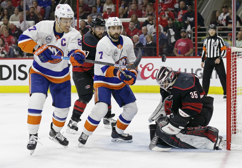 Carolina Hurricanes goalie Curtis McElhinney (35) defends the goal against New York Islanders' Anders Lee (27) and Jordan Eberle (7) while Hurricanes'