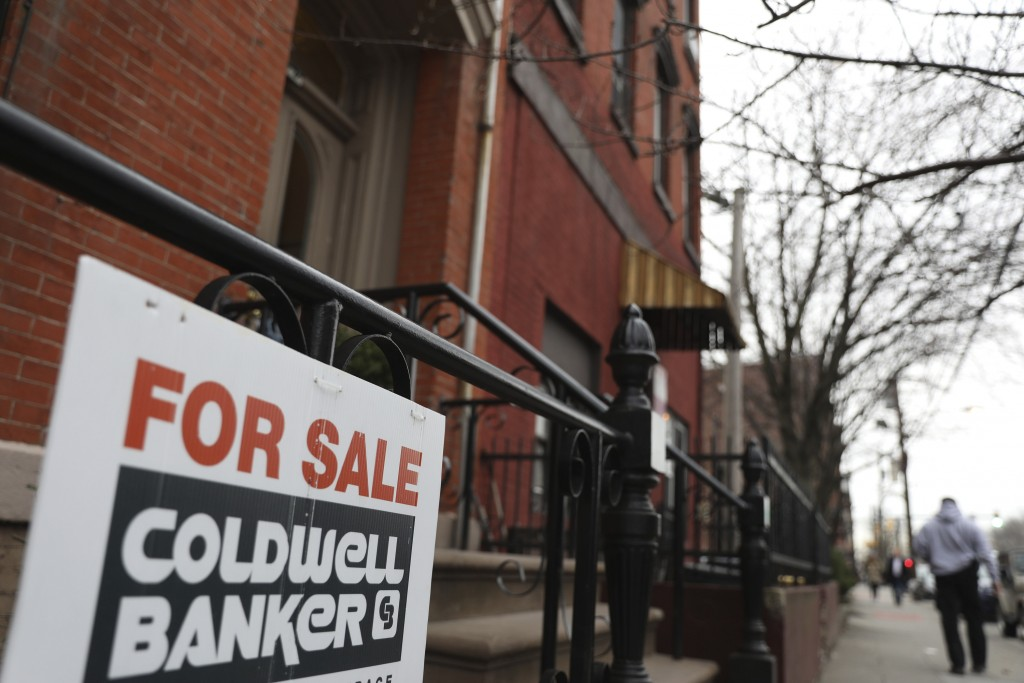 FILE - In this March 29, 2019, photo people walk by an apartment for sale in Jersey City, N.J. Americans struggling to buy their first home may face a