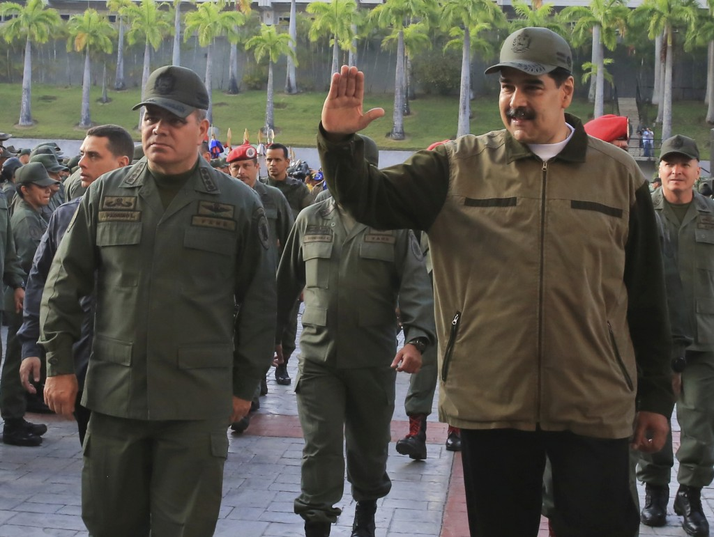 In this photo released by Miraflores Press Office, Venezuela's President Nicolas Maduro, right, accompanied by his Defense Minister Vladimir Padrino L
