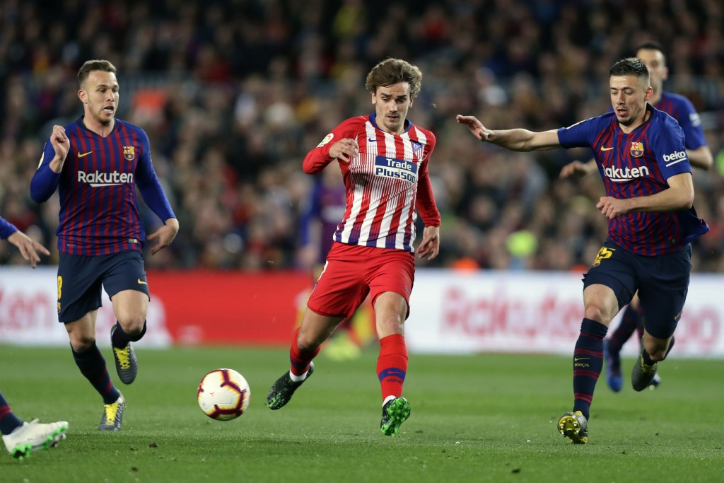 FILE - In this April 6, 2019, file photo, Atletico forward Antoine Griezmann, center, vies for the ball with Barcelona midfielder Arthur, left, and Ba