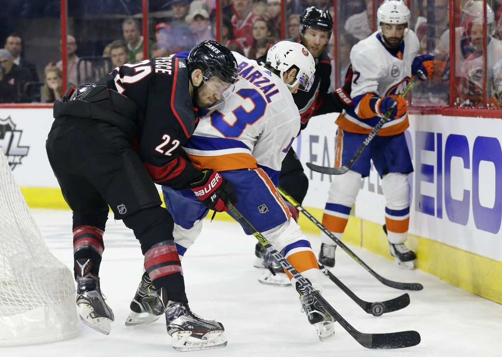 Carolina Hurricanes' Brett Pesce (22) and New York Islanders' Mathew Barzal (13) struggle for possession of the puck during the first period of Game 3...