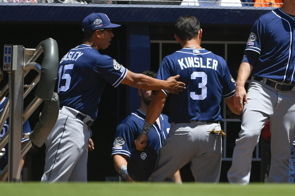 San Diego Padres' Ian Kinsler (3) is congratulated by coach Damion Easley (15) as he enters the dugout after scoring on a throwing error by Atlanta Br...