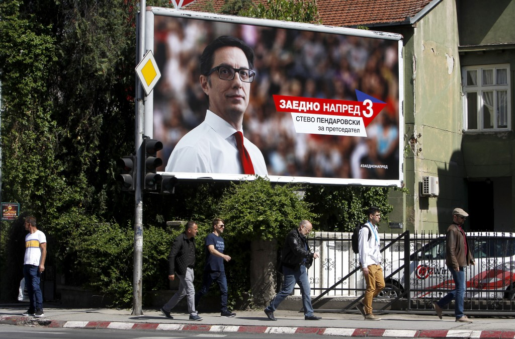 """People walk past a campaign poster of Stevo Pendarovski, a presidential candidate of the ruling coalition led by the Social Democrats, that reads: """"To"""