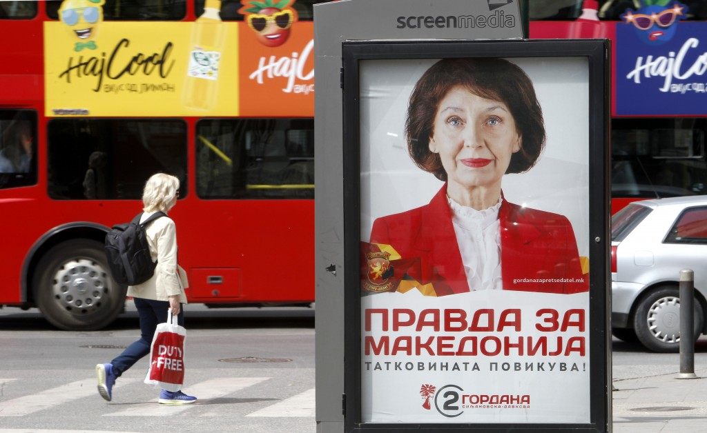 A woman walks past a poster of Gordana Siljanovska Davkova, a candidate for the opposition conservative VMRO-DPMNE party, in a street in Skopje, North