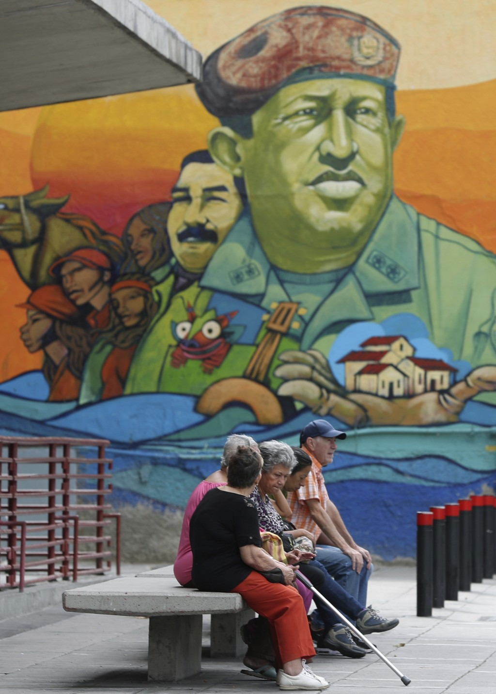 Residents rest on a bench backdropped by a mural featuring Venezuela's late President Hugo Chavez and President Nicolas Maduro, in Caracas, Venezuela,