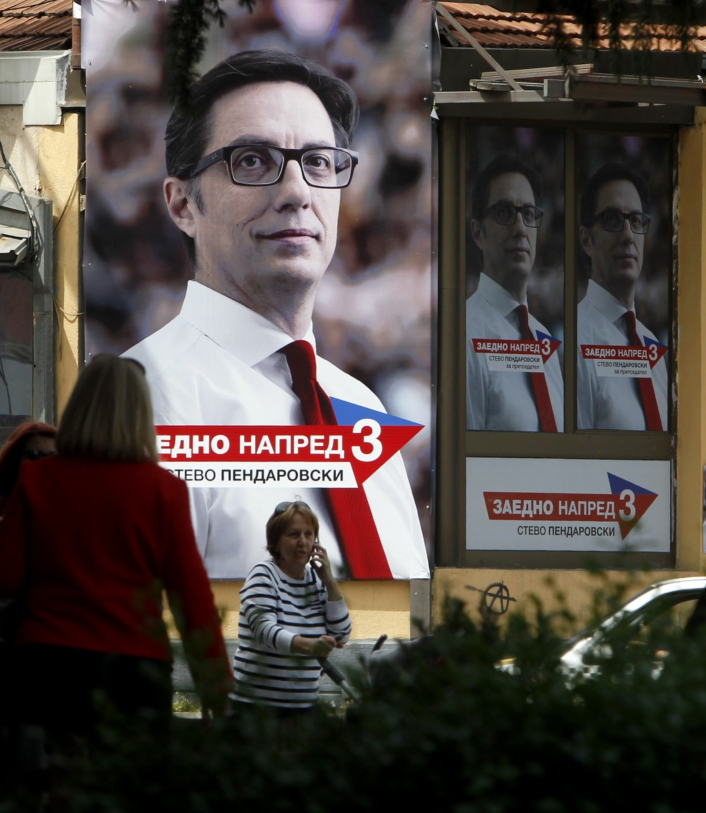 People walk past a campaign poster of Stevo Pendar...