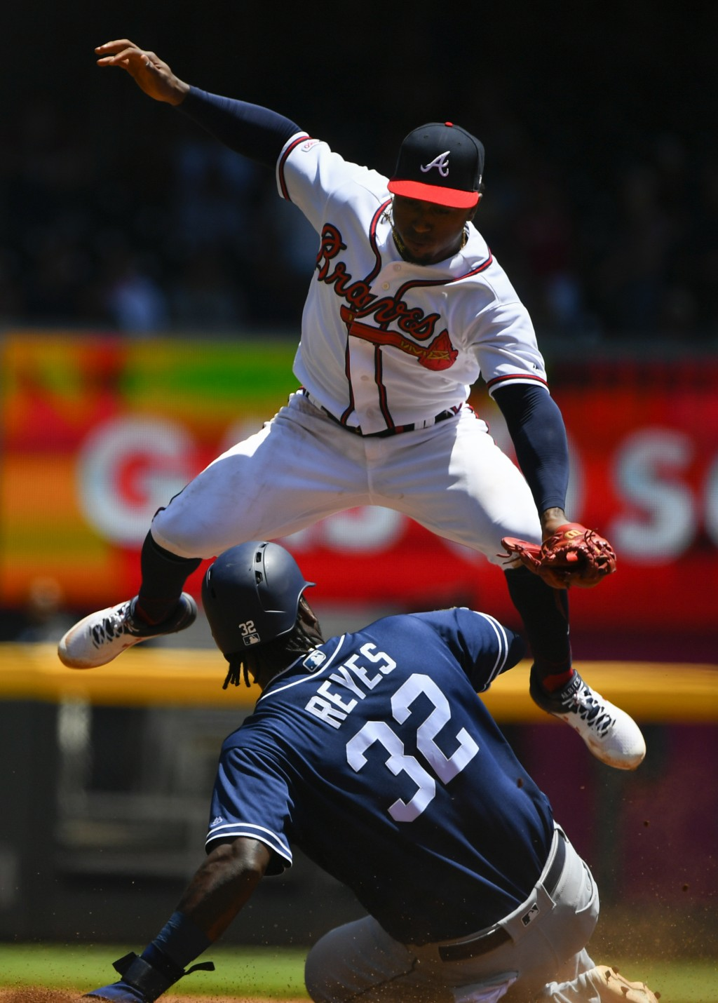 San Diego Padres' Franmil Reyes (32) is safe at second base as Atlanta Braves second baseman Ozzie Albies comes down on him after going up for a throw...