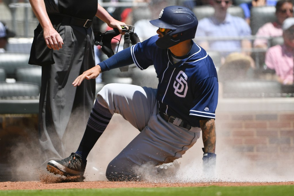 San Diego Padres' Manny Machado comes up from a slide after scoring on a Wil Myers single to left field during the fifth inning of a baseball game aga...