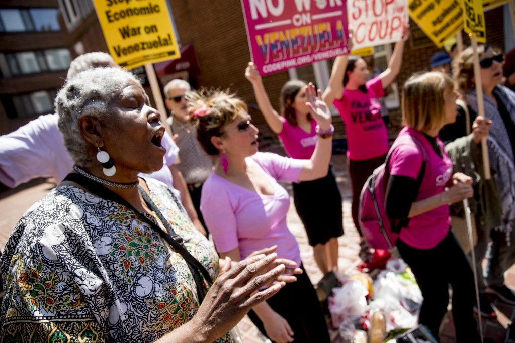 U.S. activist Medea Benjamin, co-founder of the anti-war group Code Pink, right, and others, sing together outside the Venezuelan Embassy in Washingto