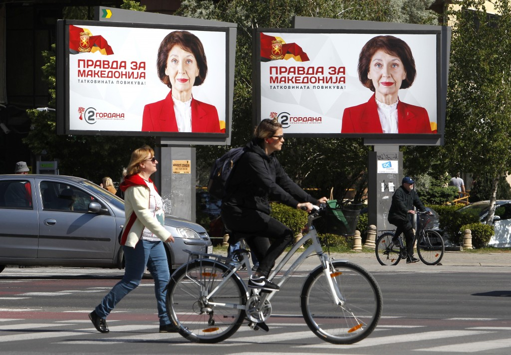 People cross a street passing campaign posters of Gordana Siljanovska Davkova, a candidate for the opposition conservative VMRO-DPMNE party that read: