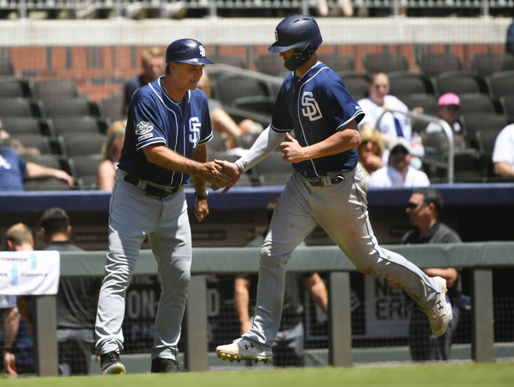 San Diego Padres' Wil Myers is congratulated by third base coach Glenn Hoffman, left, as he runs bases during his home run to right field in the sixth