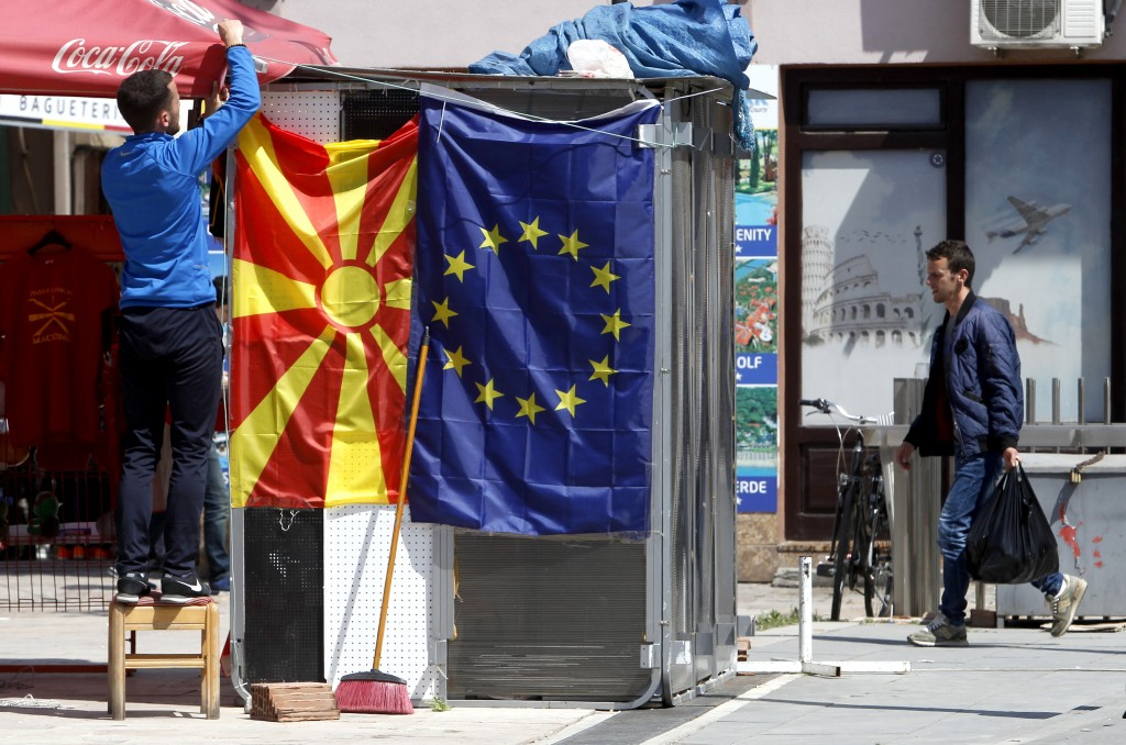 A street vendor fixes a North Macedonia flag next to an EU flag in a street in Skopje, North Macedonia, Friday, May 3, 2019. Voters in newly-renamed N