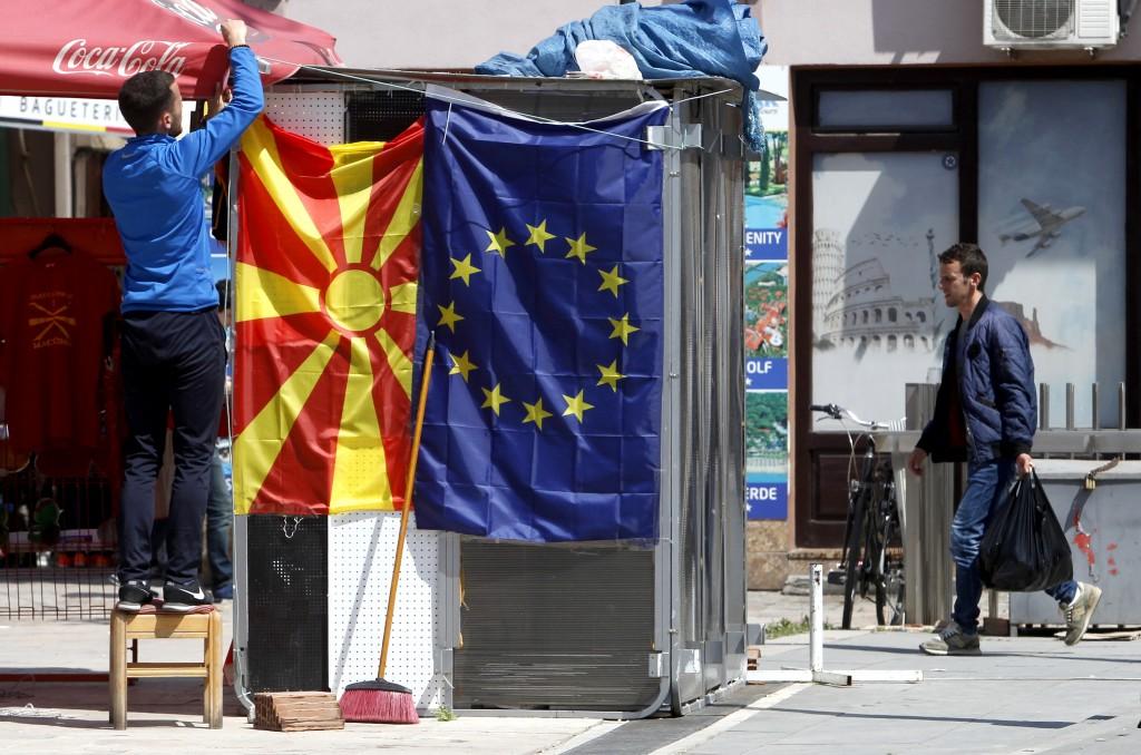 A street vendor fixes a North Macedonia flag next ...